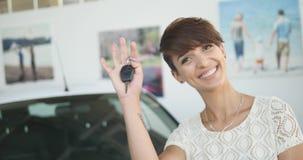 De jonge sleutels van de vrouwenholding tot nieuwe autoauto en het glimlachen bij camera stock foto