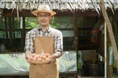 De jonge slimme van de de plaid lange koker van de landbouwersslijtage het overhemds bruine schort houdt verse kippeneieren in ma stock fotografie