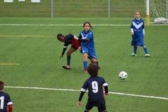 De jonge spelers spelen voetbal stock afbeelding