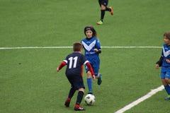 De jonge spelers spelen voetbal stock afbeeldingen