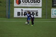 De jonge spelers spelen voetbal stock foto's