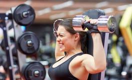 De jonge spieren van de vrouwenverbuiging met domoor in gymnastiek Royalty-vrije Stock Foto's