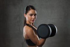 De jonge spieren van de vrouwenverbuiging met domoren in gymnastiek Royalty-vrije Stock Fotografie