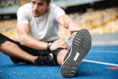 De jonge sportenmens bij het stadion maakt uitrekkende oefeningen stock foto's