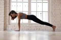 De jonge sportieve aantrekkelijke vrouw het praktizeren yoga, Plank stelt stock afbeeldingen