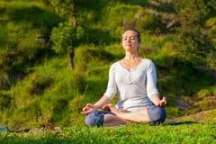 De jonge sportieve geschikte vrouw die yoga Lotus doen stelt oudoors Royalty-vrije Stock Afbeeldingen