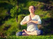 De jonge sportieve geschikte vrouw die yoga Lotus doen stelt oudoors Stock Afbeeldingen