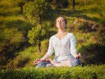 De jonge sportieve geschikte vrouw die yoga Lotus doen stelt oudoors Stock Fotografie