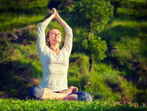 De jonge sportieve geschikte vrouw die yoga Lotus doen stelt oudoors Stock Afbeelding
