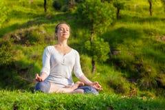 De jonge sportieve geschikte vrouw in yoga Lotus stelt oudoors Royalty-vrije Stock Afbeelding