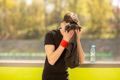 De jonge sportieve mens die en zijn zweet rusten afvegen met een handdoek na trainingsport oefent in openlucht uit stock foto