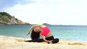 De jonge sportieve vrouw doet uitrekkende oefening op het strand dichtbij het overzees Gezond Actief Levensstijlconcept stock videobeelden
