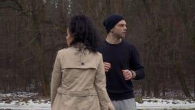 De jonge sportman komt met jong meisje in botsing terwijl hij ` s doornemend zebrapad stock video