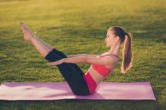 De jonge sportvrouw maakt abs training terwijl binnen het uitoefenen van yoga royalty-vrije stock fotografie