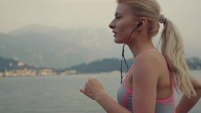 De jonge sportvrouw zet op haar oortelefoons en begint de looppas aan de grote ochtend stock video