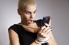 De jonge stedelijke vrouw wijdde zich aan slimme telefoonmetafoor Stock Foto's