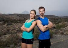 De jonge stellende schouder die van het sportpaar aan schouder koele en uitdagende houding kijken stock fotografie