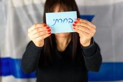 De jonge Stemming Front Of Face van de Vrouwenholding op Isra?lische Vlagachtergrond Hebreeuwse tekst die ik bij het stemmen van  stock foto's