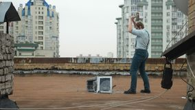De jonge sterke mens breekt de monitor met een voorhamer op het dak Hamer, geweld, haat, anarchie, vernietiging 60 stock video