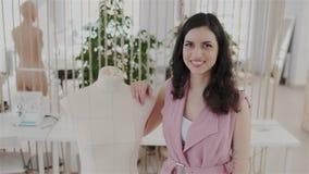 De jonge stilist van de vrouwendoek in modieus of toevallig kijkt zich bevindt met ledenpop in eigen kleermakerswerkruimte, kijkt stock videobeelden