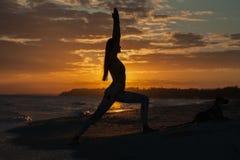 De jonge strijder en de held van de vrouwen praktizerende yoga stellen bij zonsondergang, zonsopgang Zenwellness en welzijnsconce Stock Fotografie