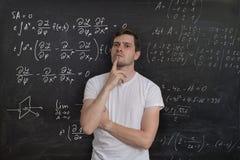 De jonge student denkt en lost wiskundig probleem op Wiskundeformule op bord op achtergrond Royalty-vrije Stock Foto