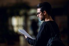De jonge student informatica raadpleegt sommige die documenten door het licht van het scherm in een gang worden verlicht royalty-vrije stock foto's
