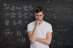 De jonge student lost wiskundeexamen op Wiskundeformule op bord op achtergrond Royalty-vrije Stock Afbeelding
