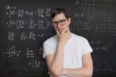De jonge student lost wiskundeexamen op Wiskundeformule op bord op achtergrond Stock Foto's