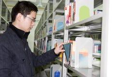 De jonge student vindt boeken in bibliotheek Royalty-vrije Stock Afbeeldingen
