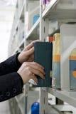 De jonge student vindt boeken in bibliotheek Stock Fotografie
