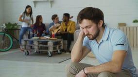De jonge studentenkerel voelt verstoord en geïsoleerd terwijl zijn vrienden die partij thuis binnen vieren stock video