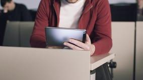 De jonge studentenzitting bij bureau staat met tabletcomputer in wisselwerking en leest boeken voorraad Onderwijs universiteit stock footage