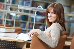 De jonge studie van het studentenmeisje met boek in bibliotheek Stock Afbeelding