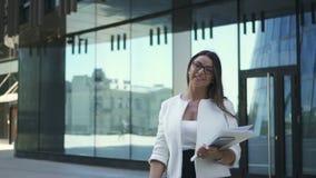 De jonge succesvolle advocaat bekijkt het smartphonescherm, die op moderne de bouwachtergrond stellen stock footage
