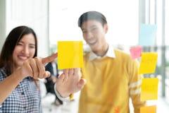 De jonge succesvolle creatieve man en de vrouw glimlachen en uitwisseling van ideeën op project op kantoor royalty-vrije stock fotografie
