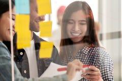 De jonge succesvolle creatieve vrouw en het team glimlacht en uitwisseling van ideeën op project op kantoor stock foto's