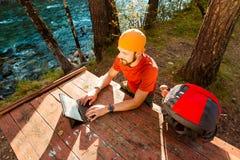 De jonge, succesvolle, gebaarde mens, het zitten lijst door de rivier en werkt aan tablet, in openlucht stock foto