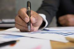 De jonge succesvolle pen die van de mensenholding marketing grafiek in mo analyseren Stock Foto's