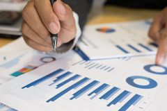 De jonge succesvolle pen die van de mensenholding marketing grafiek in mo analyseren Stock Afbeelding