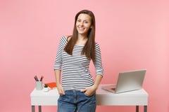 De jonge succesvolle vrouwenholding dient zakken het werk en status dichtbij wit die bureau met PC-laptop in op pastelkleurroze w stock afbeeldingen