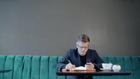 De jonge succesvolle zakenman gebruikt telefoon, schrijft, zittend bij lijst in koffie stock footage