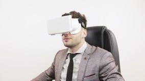 De jonge succesvolle zakenman zet virtuele werkelijkheidsbeschermende brillen