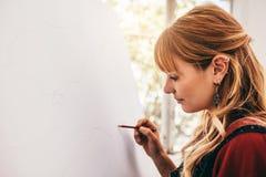 De jonge tekening van de vrouwenkunstenaar met potlood royalty-vrije stock afbeelding