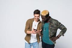 De jonge telefoon van het twee internationale die vriendengebruik op witte achtergrond wordt geïsoleerd Multiraciale vriendschap royalty-vrije stock fotografie