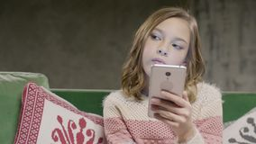 De jonge telefoon van de meisjesholding in handen die in ruimte zitten stock videobeelden