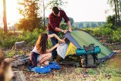 De jonge tent van de paarvestiging in openlucht, wandeling en het kamperen stock foto's