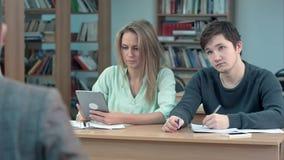 De jonge tiener gebruikt tablet terwijl het leren in klasse stock footage