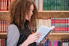 de jonge tiener kiest een boek in de opslag stock foto's