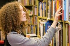 de jonge tiener kiest een boek in de opslag Royalty-vrije Stock Afbeeldingen